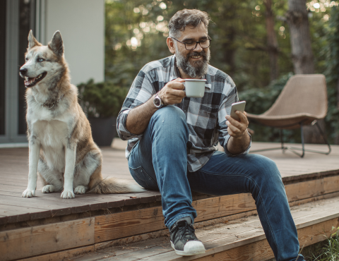 Man using phone with nearby dog