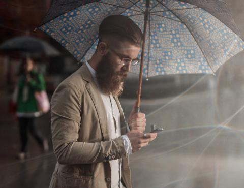 Man using phone while holding an umbrella